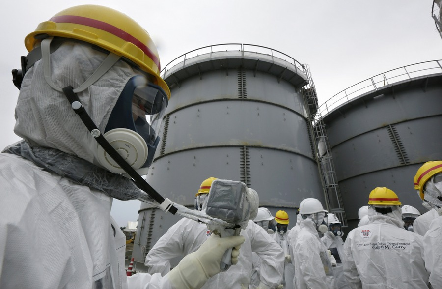 TEPCO employee uses a survey meter near storage tanks for radioactive water in the H4 area in Fukushima